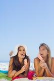 Donne graziose sorridenti che si trovano sul loro asciugamano che mangia il gelato fotografie stock