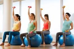Donne incinte felici che si esercitano sul fitball in palestra Immagine Stock Libera da Diritti