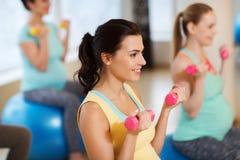 Donne incinte felici che si esercitano sul fitball in palestra Immagini Stock