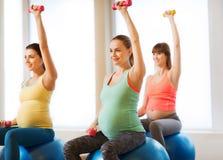 Donne incinte felici che si esercitano sul fitball in palestra fotografia stock libera da diritti