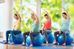 Donne incinte felici che si esercitano sul fitball in palestra Fotografie Stock