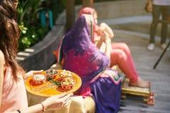 Donne indiane che tengono vassoio con gli oggetti di preghiera con la sposa indiana nel fondo confuso Fotografia Stock
