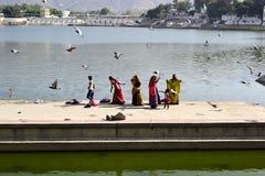 Donne indiane con i bambini dopo abluzione religiosa nel lago santo Immagini Stock