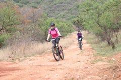 Donne invecchiate mezzo che godono all'aperto del giro alla corsa del mountain bike Fotografia Stock
