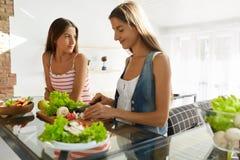Donne mangianti in buona salute che cucinano insalata in cucina Alimento di dieta di forma fisica Fotografie Stock