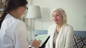 Donne mature malate di giovane visita dell'infermiere alla sua casa archivi video