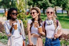 Donne multiculturali con le tazze di caffè eliminabili in mani che camminano nel parco Fotografia Stock