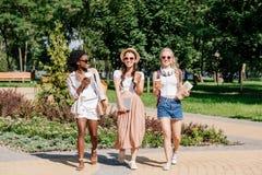Donne multiculturali con le tazze di caffè eliminabili in mani che camminano nel parco Fotografie Stock Libere da Diritti