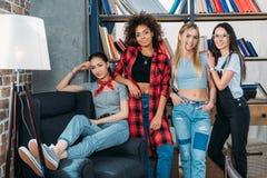 Donne multietniche alla moda che posano insieme a casa biblioteca Fotografia Stock