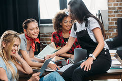 Donne multietniche che lavorano mentre sedendosi alla tavola in Ministero degli Interni Fotografia Stock Libera da Diritti