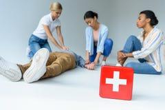 donne multietniche su addestramento del pronto soccorso, cassetta di pronto soccorso su priorità alta, Fotografia Stock