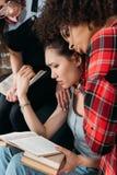 Donne multietniche turbate che abbracciano e che tengono i libri Fotografia Stock
