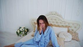Donne nel cattivo umore, ribaltamento e nel gridare, sedentesi sul letto in camere da letto spaziose fotografia stock