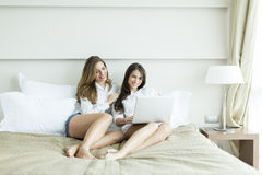 Donne nel letto con il computer portatile Immagine Stock Libera da Diritti
