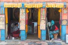Donne nepalesi che fanno la pittura fatta a mano del panno nel negozio fotografie stock