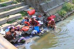 Donne nepalesi che lavano i vestiti lungo il fiume Immagine Stock