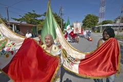 Donne più anziane e bambini che marciano tramite le vie del Morelos di Puerto che portano bandiera messicana e le statue cattolic Immagini Stock