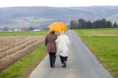 Donne in pioggia sotto un ombrello Fotografia Stock
