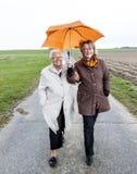 Donne in pioggia sotto un ombrello Immagini Stock