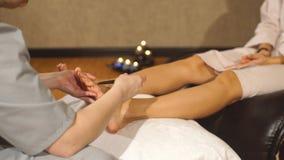 Donne a reflessologia che ha piede massaggiato o urgente con il bastone di legno stock footage