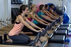 Donne risolute che praticano allungando esercizio sul riformatore Immagine Stock