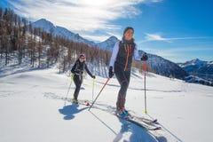 Donne in salita con alpinismo delle pelli e dello sci della guarnizione Fotografia Stock
