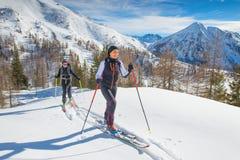Donne in salita con alpinismo delle pelli e dello sci della guarnizione Fotografie Stock Libere da Diritti