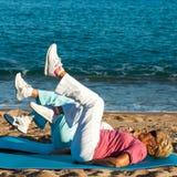 Donne senior che fanno gli esercizi di gamba sulla spiaggia. Immagini Stock