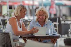 Donne senior che si rilassano in caffè e che per mezzo della compressa digitale immagini stock libere da diritti