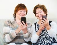 Donne senior con i telefoni cellulari Fotografia Stock