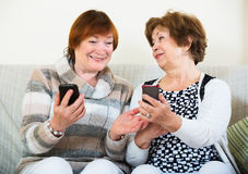 Donne senior con i telefoni cellulari Immagine Stock