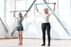 Donne serie sicure che risolvono con un bastone relativo alla ginnastica Immagine Stock