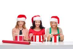 Donne sorridenti in cappelli dell'assistente di Santa con i contenitori di regalo Immagine Stock