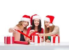 Donne sorridenti in cappelli dell'assistente di Santa con i contenitori di regalo Immagine Stock Libera da Diritti