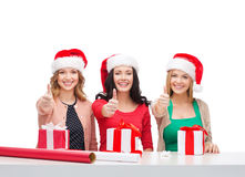 Donne sorridenti in cappelli dell'assistente di Santa con i contenitori di regalo Fotografie Stock Libere da Diritti