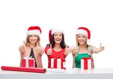 Donne sorridenti in cappelli dell'assistente di Santa con i contenitori di regalo Fotografia Stock Libera da Diritti