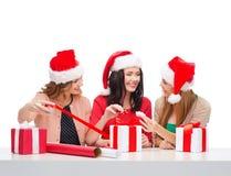 Donne sorridenti in cappelli dell'assistente di Santa con i contenitori di regalo Fotografia Stock