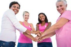 Donne sorridenti che indossano i nastri del cancro al seno che mettono il togeth delle mani Immagine Stock