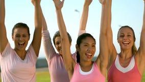 Donne sorridenti che indossano rosa per cancro al seno ed incoraggiare video d archivio