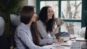 Donne sorridenti che lavorano al computer nell'ufficio stock footage