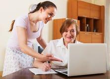 Donne sorridenti che sembrano i documenti finanziari in computer portatile Immagine Stock Libera da Diritti