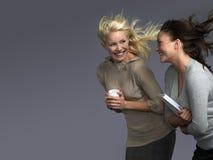 Donne sorridenti con capelli che soffiano in vento Immagini Stock
