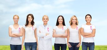 Donne sorridenti con i nastri rosa di consapevolezza del cancro Immagini Stock