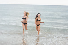 Donne sorridenti del bikini che corrono in acqua alla spiaggia Fotografia Stock