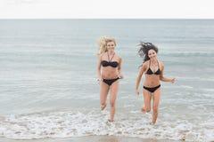 Donne sorridenti del bikini che corrono in acqua alla spiaggia Fotografie Stock