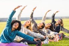 Donne sportive che allungano durante la classe di forma fisica Immagini Stock Libere da Diritti