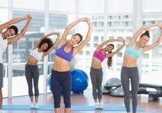 Donne sportive che allungano le mani alla classe di yoga Immagine Stock Libera da Diritti