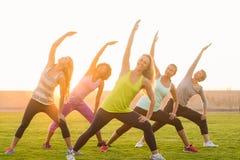 Donne sportive che si scaldano durante la classe di forma fisica Immagini Stock