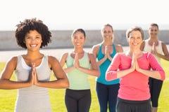 Donne sportive sorridenti che fanno posizione di preghiera nella classe di yoga Immagine Stock