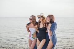Donne sulla spiaggia con il plaid dopo avere uguagliato, vacanze estive, feste, viaggio immagine stock libera da diritti